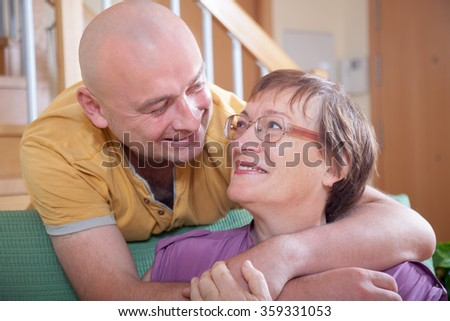 Mature mother with adult son on  couch in  living room.