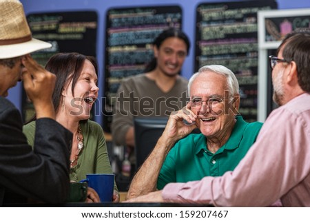 Mature people in a coffee house laughing