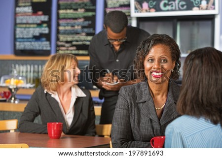 Mature smiling business woman with friend in cafe
