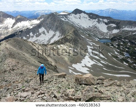 Mature woman ascending alpine ridge toward the summit of Chair Mountain Raggeds Wilderness Colorado