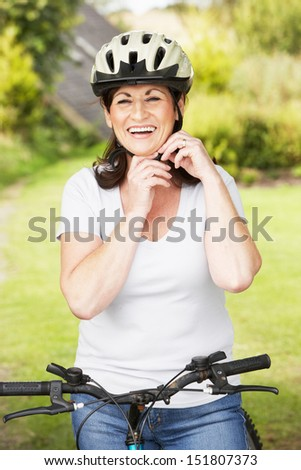 Mature Woman On Cycle Ride In Countryside