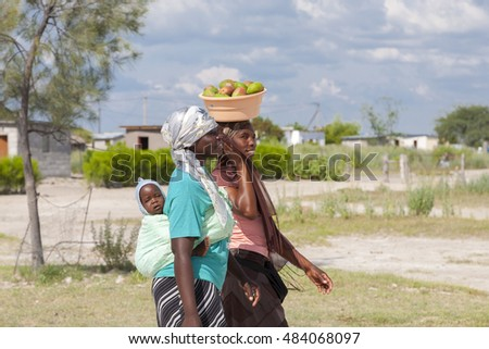MAUN, BOTSWANA, DEC 28: Beautiful black African women walking with headscarf, traditional village in the background. Botswana 2019