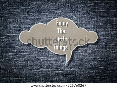 Meaningful quote on paper cloud with blue denim background, Enjoy the little things.