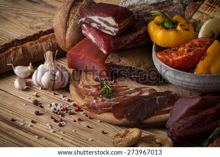 Meat jerky and grilled vegetables on a wooden background