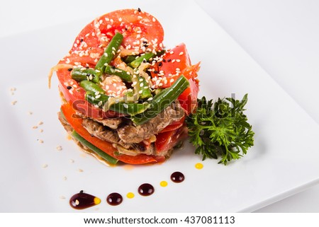 meat salad, tomato decoration on a white plate