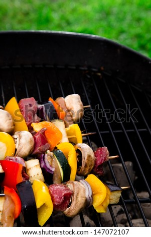 Meat spits on grill flames in background