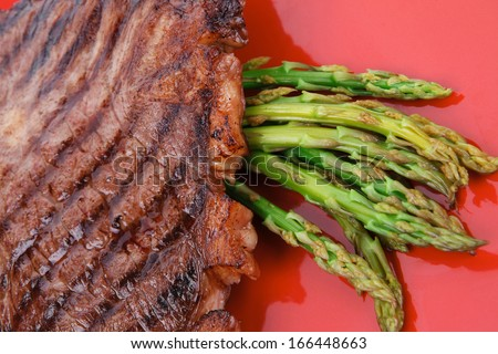 Meat Table Grilled Beef Fillet With Asparagus Served On Red Dish Isolated Over White