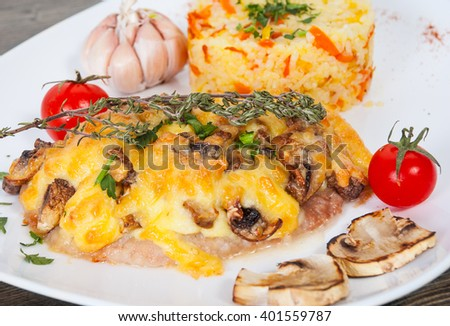 Meat under cheese and mushrooms with rice
