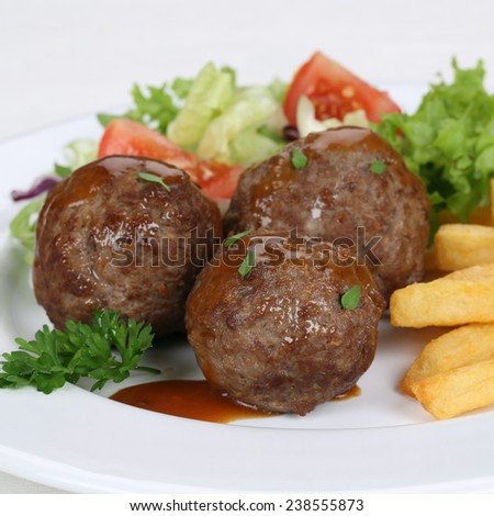 Meatballs meal with french fries, salad and lettuce on plate