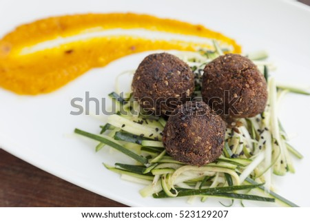 Meatballs with thinly sliced lentils and pumpkin dressing.