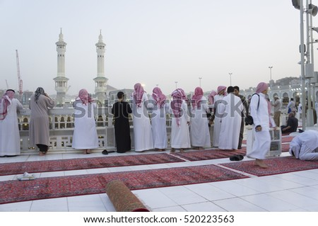 MECCA, S.ARABIA-CIRCA FEBRUARY 2012: Muslim Arab men in white garb and red keffiyeh look below in Makkah, Saudi Arabia.