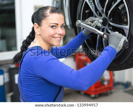 Mechanic changing the wheel on a car hydraulic lift