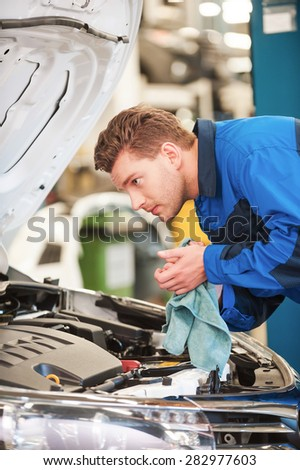 Mechanic examining car. Confident young man in uniform examining car and wiping his hands with rag while standing in workshop