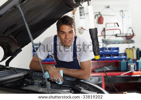 mechanic leaning on bonnet and looking at camera
