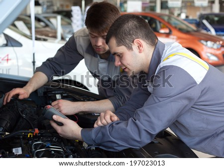 Mechanics at repair shop. Top view of two confident mechanics working on a car engine. Selective focus.