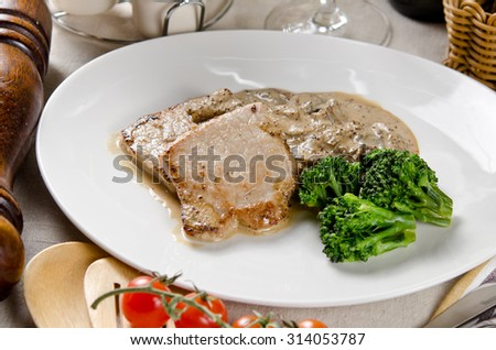 medallions of pork stewed with mushrooms in a creamy garlic sauce