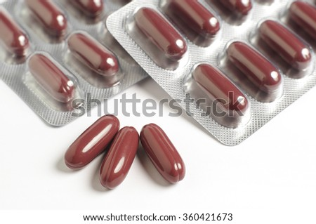 Medical capsules closeup. Pile of brown tablets on white background