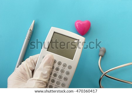 Medicine concept - medical insurance - sterile gloves, stethoscope, calculator, pen and heart
