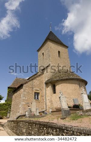 Medieval church in French village with cemetary and stone cross