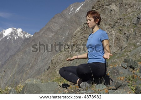 Meditating girl in the mountains