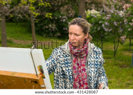 Melancholy female artist working  on a trestle and easel painting with oils and acrylics during an art class in a park