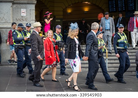 Melbourne, Australia - November 3, 2015: racegoers returning from Flemington Racecourse and Protective Services Officers in front of Flinders Street Station on Melbourne Cup Day.