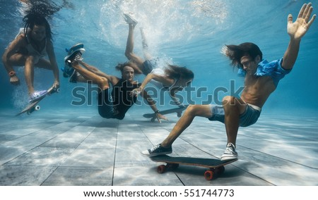 Men and Women skateboarding underwater in the swimming pool