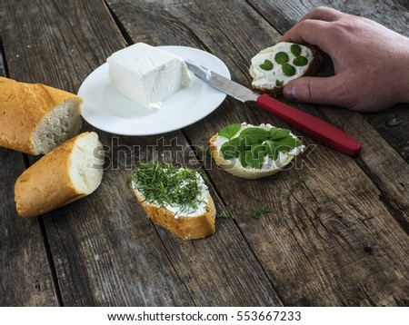 men's hand take bruschetta with feta cheese and chopped spicy herbs on an old wooden weathered table