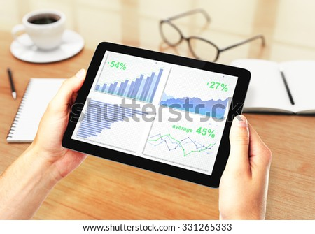 Men's hands holding a digital tablet with financial charts