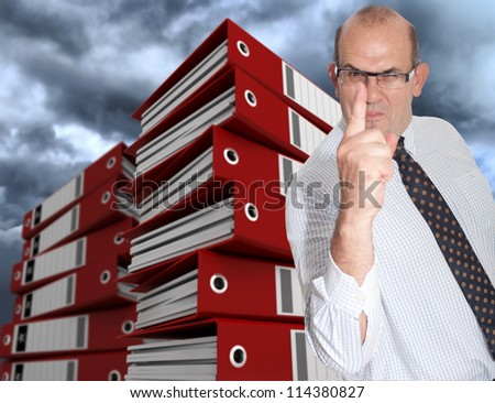 Menacing business man surrounded by piles of folders and a stormy sky