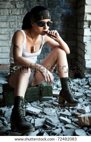 Mercenary woman with a big cigar on the brick wall background.