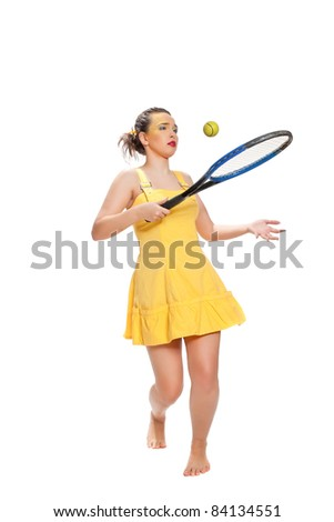 Merry beautiful girl in a yellow dress with a tennis racket posing on a white background