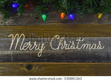 Merry Christmas in rope design on rustic barn wood with string of holiday lights