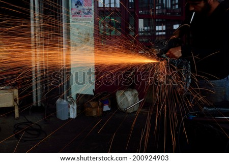 MERSIN, TURKEY - JUNE 11: Electric machine, iron cutting undefined male employees on June 11, 2014 in Mersin, Turkey. Iron working industry is one of the most heavy-duty jobs.