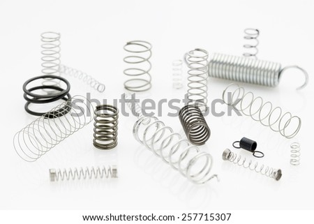 mess arrangement of selection of metal springs laying or standing on white reflective background