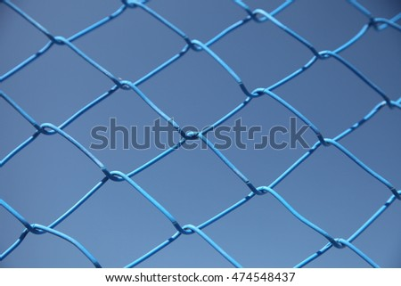 Metal fence blue grid against a blue sky