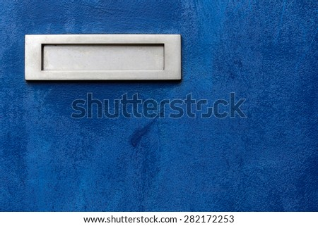 Metal letter box on blue background.