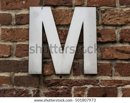 Metal letter M on a brick wall