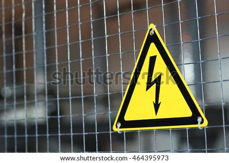 Metal mesh and yellow electrical danger sign.