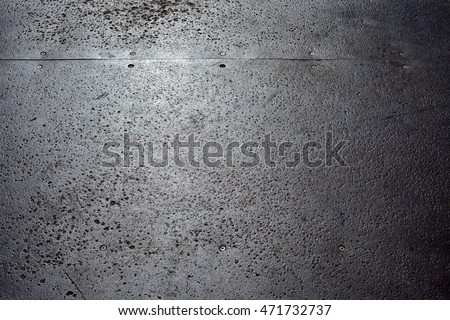 Metal texture background. Steel plate pitted and corroded by use on an outdoor skateboard half-pipe. Close up.