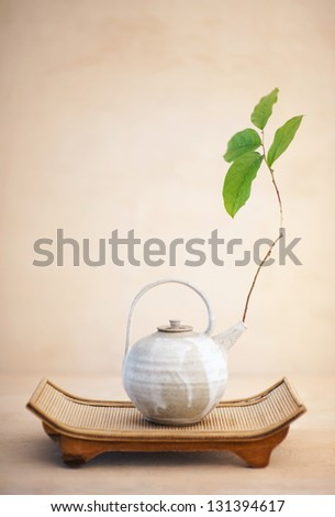 Metta or Lovingkindness.Still life photography of a beautiful asian teapot with a branch of  Spring leaves set upon an organic bamboo tray.