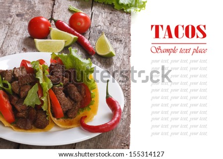 Mexican tacos with chili and lime on a wooden table
