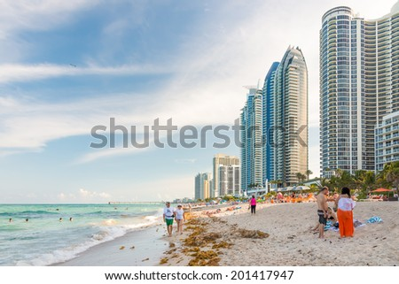 MIAMI,USA - MAY 26,2014 : Tourists and locals enjoying the beach at Miami with a view of the skyscrapers next to the shore