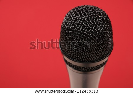 Microphone on red background.