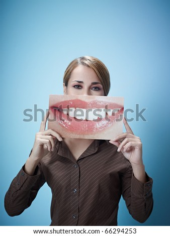 mid adult business woman holding photo of toothy smile on blue background. Vertical shape, front view, waist up, copy space