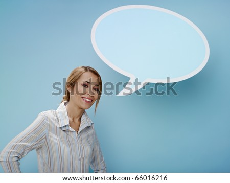 mid adult business woman standing near blank speech bubble on blue background. Horizontal shape, front view, waist up, copy space