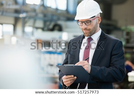Mid adult businessman writing on clipboard in metal industry