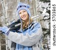Mid adult Caucasian female skier wearing blue ski clothing carrying skis on shoulder. - stock photo