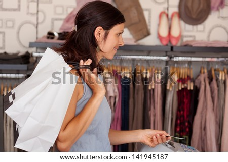 Mid adult female customer with shopping bags paying with credit card in boutique