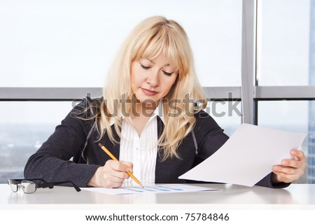 Mid adult woman sitting at a table in the office against the window and work ...